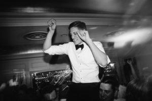 groom riding shoulders on dancefloor