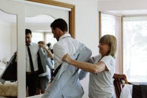 mum helping groom put on jacket