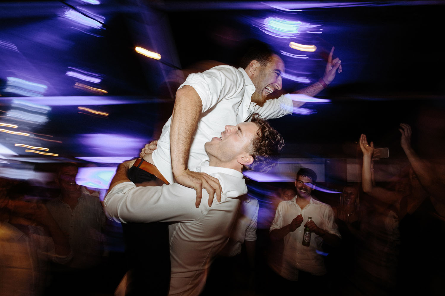 groomsman lifts groom up on dancefloor