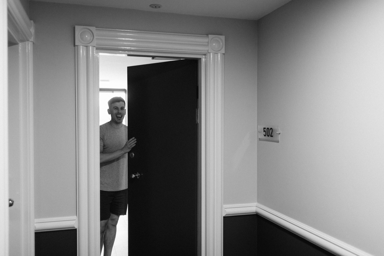 groom opening door and laughing