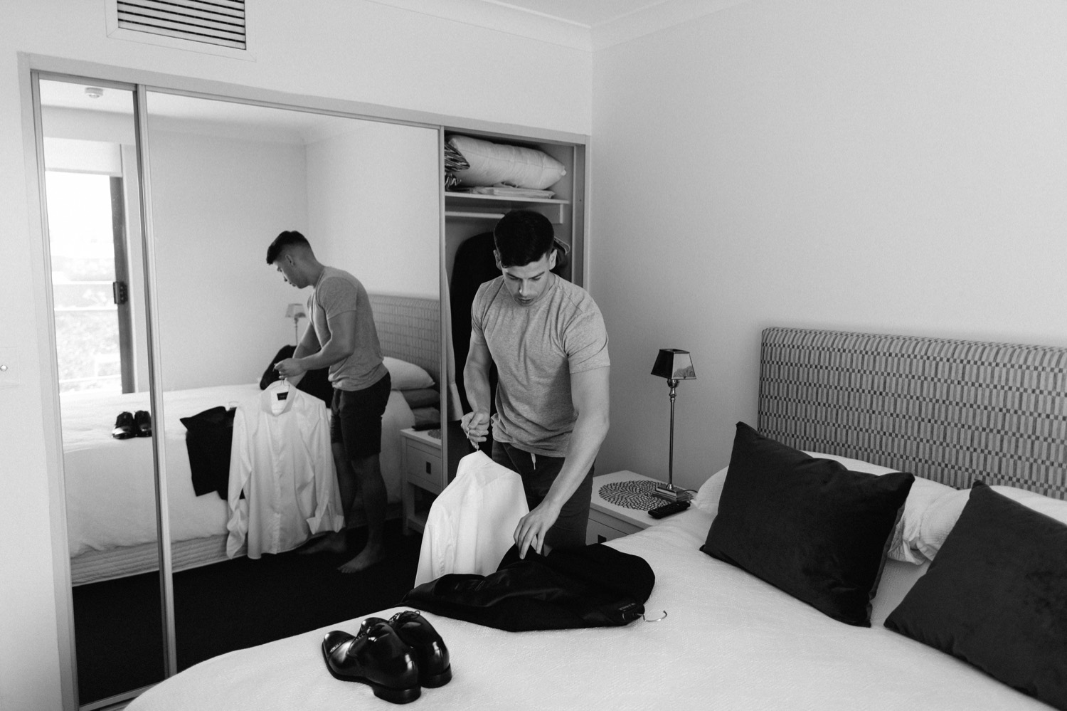 groom placing this suit & shoes on bed