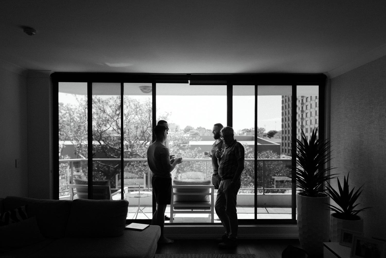 wide shot of groom and groomsman enjoying drink on balcony