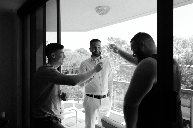 groom and groomsman sharing a cheers