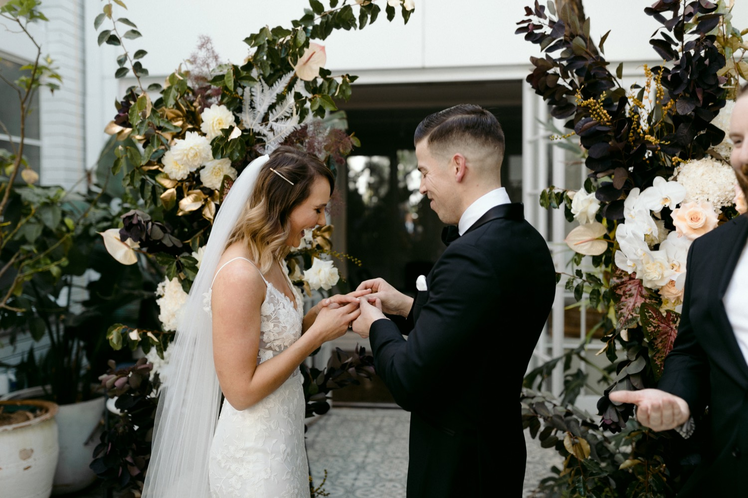 bride placing ring on grooms hand at la porte space