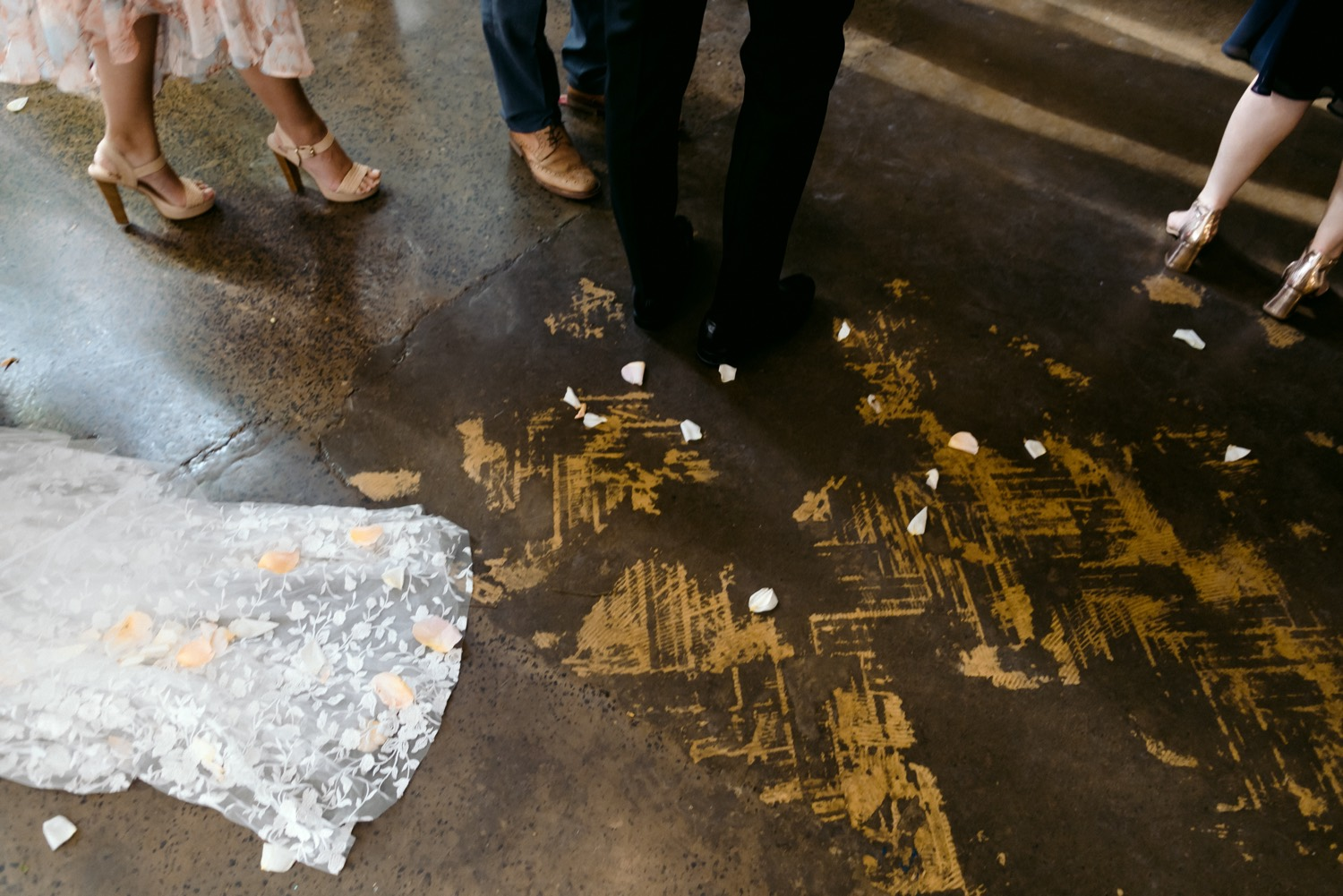photo of floor showing confetti petals and brides dress
