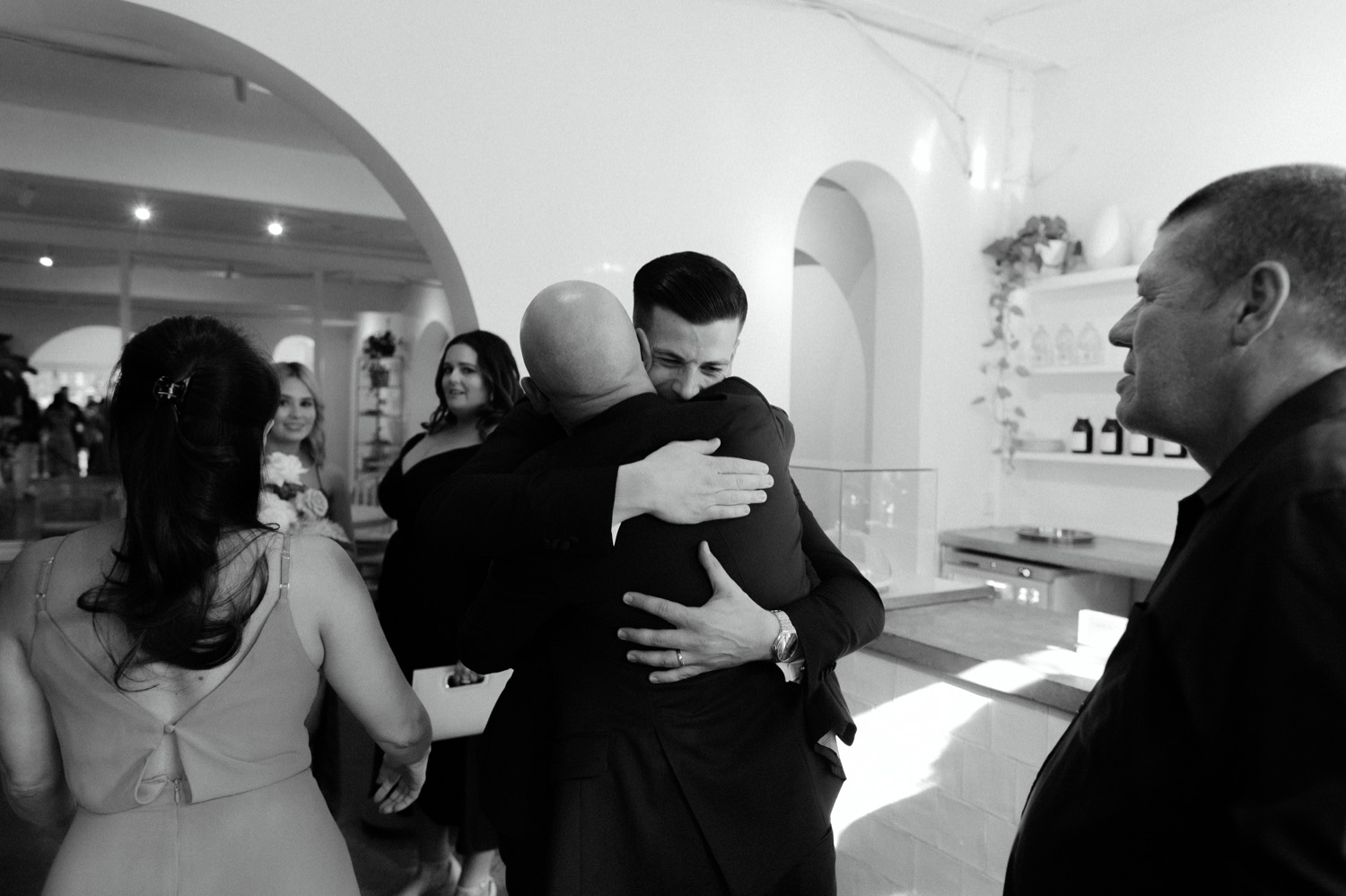 groom firmly hugging guest after ceremony