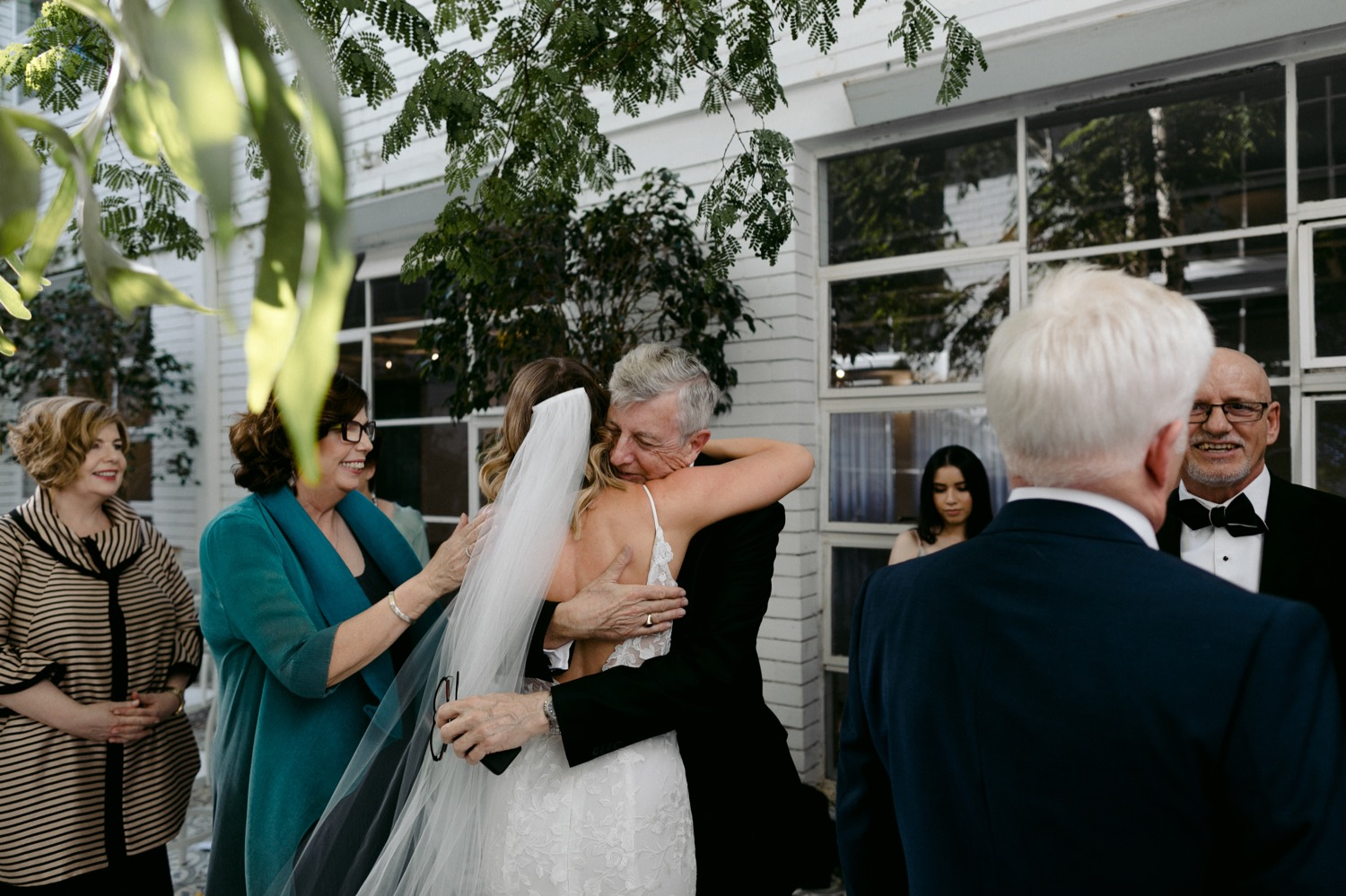 bride hugging grooms father at the end of wedding ceremony