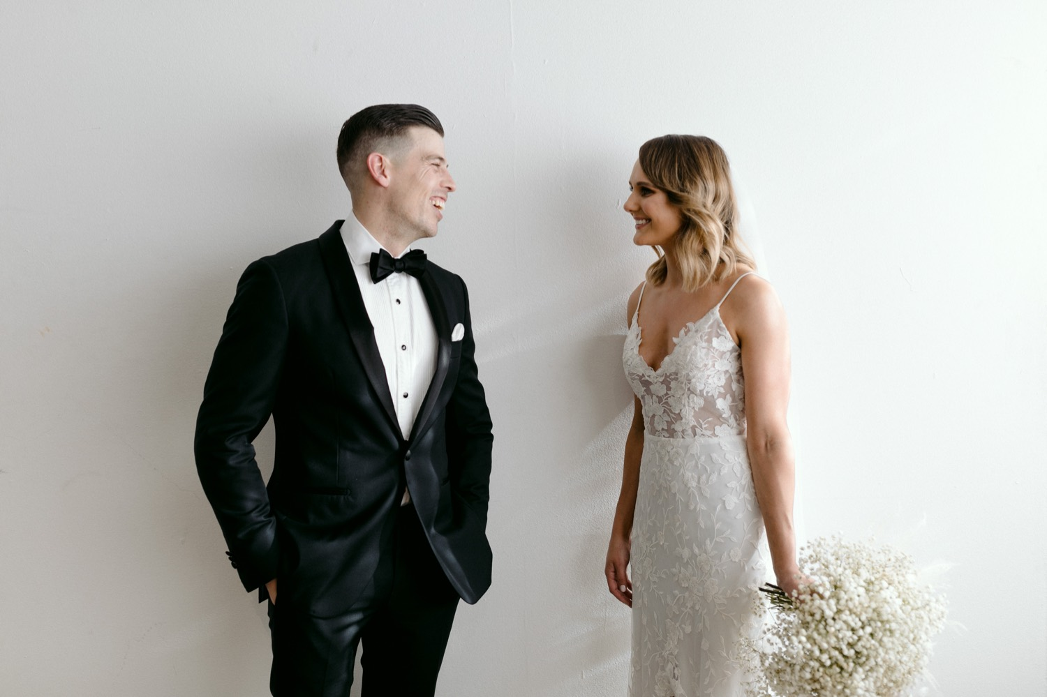 portrait of the bride and groom in black tie laughing