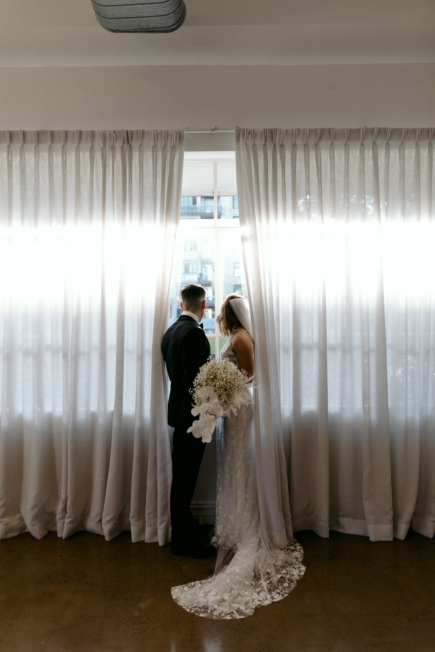 bride and groom looking out of la porte space window at guests below