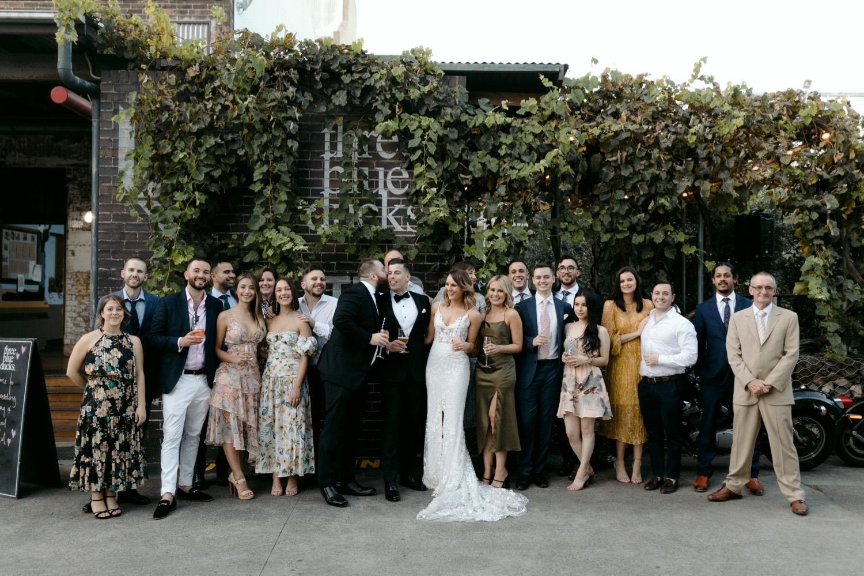 wedding group photo outside three blue ducks building