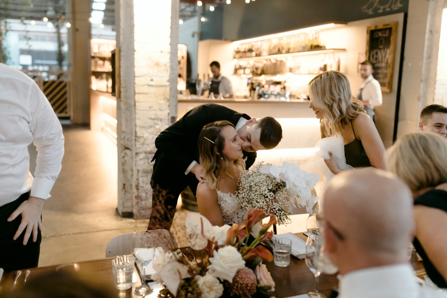 groom hugging a sat bride from behind as she laughs