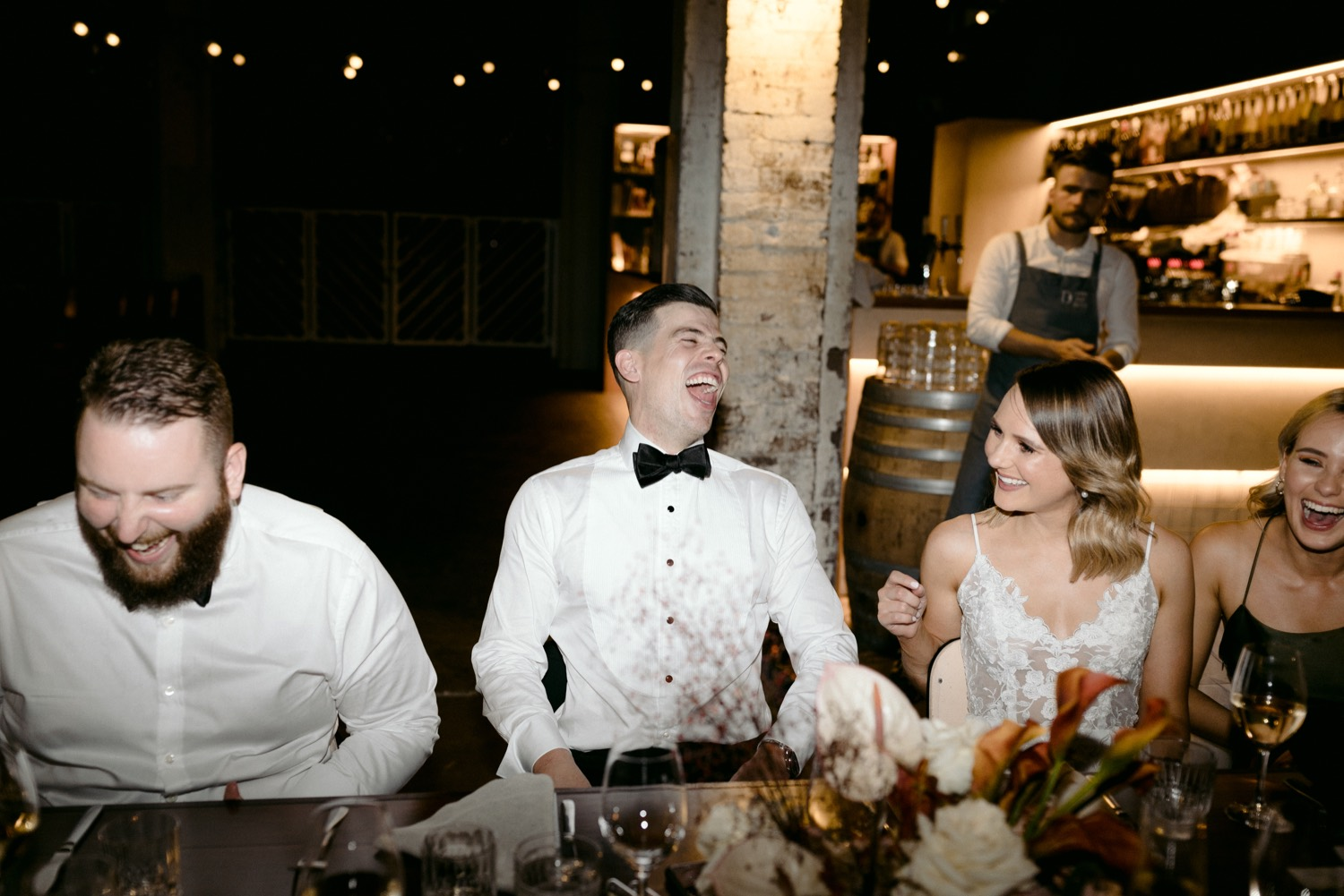 groom laughing in black tie during the speeches