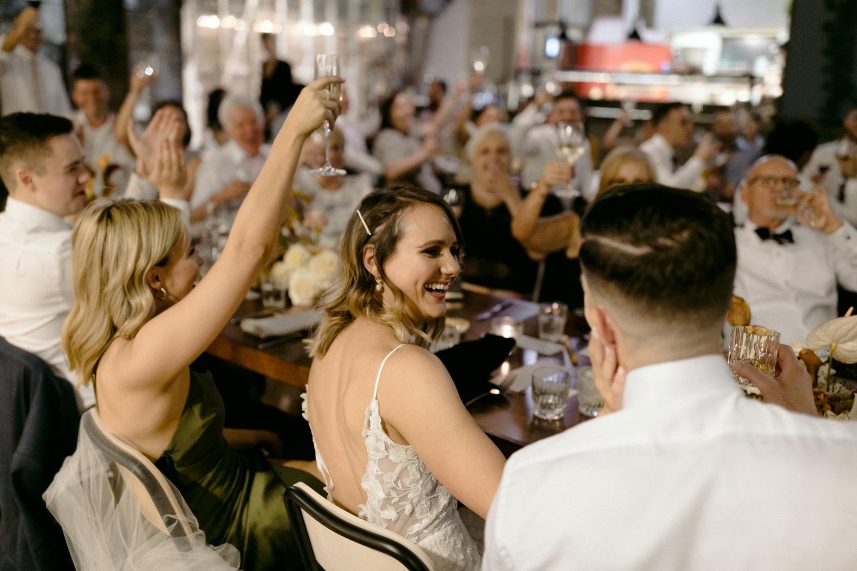 bride tenderly stroking grooms face as crow around cheer
