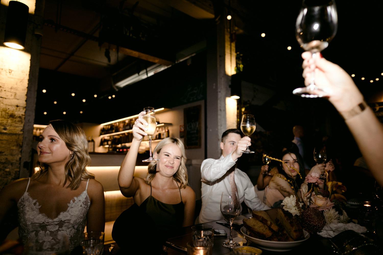 bridal party cheers at three blue ducks wedding reception