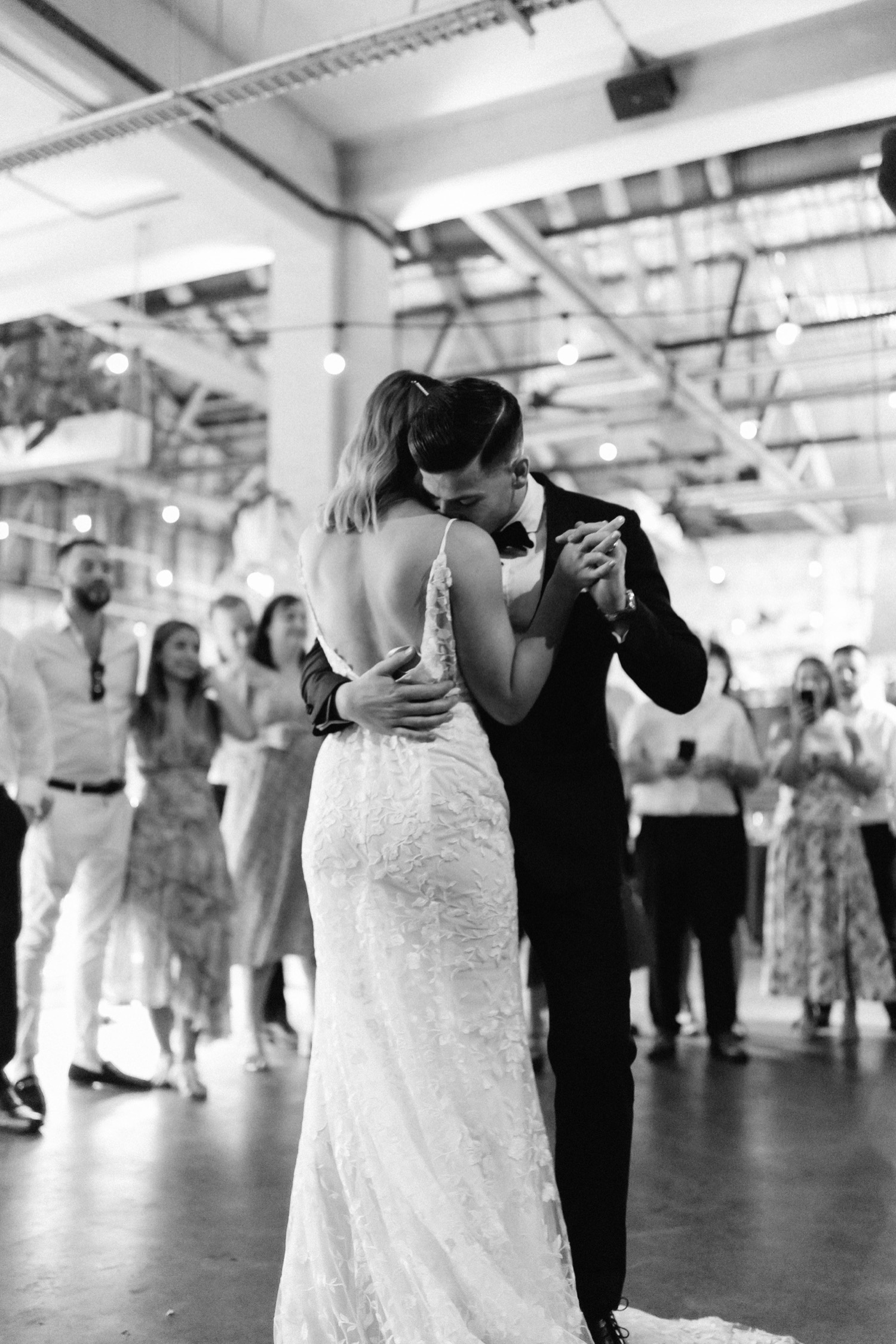 groom kissing bride on her shoulder during the first dance
