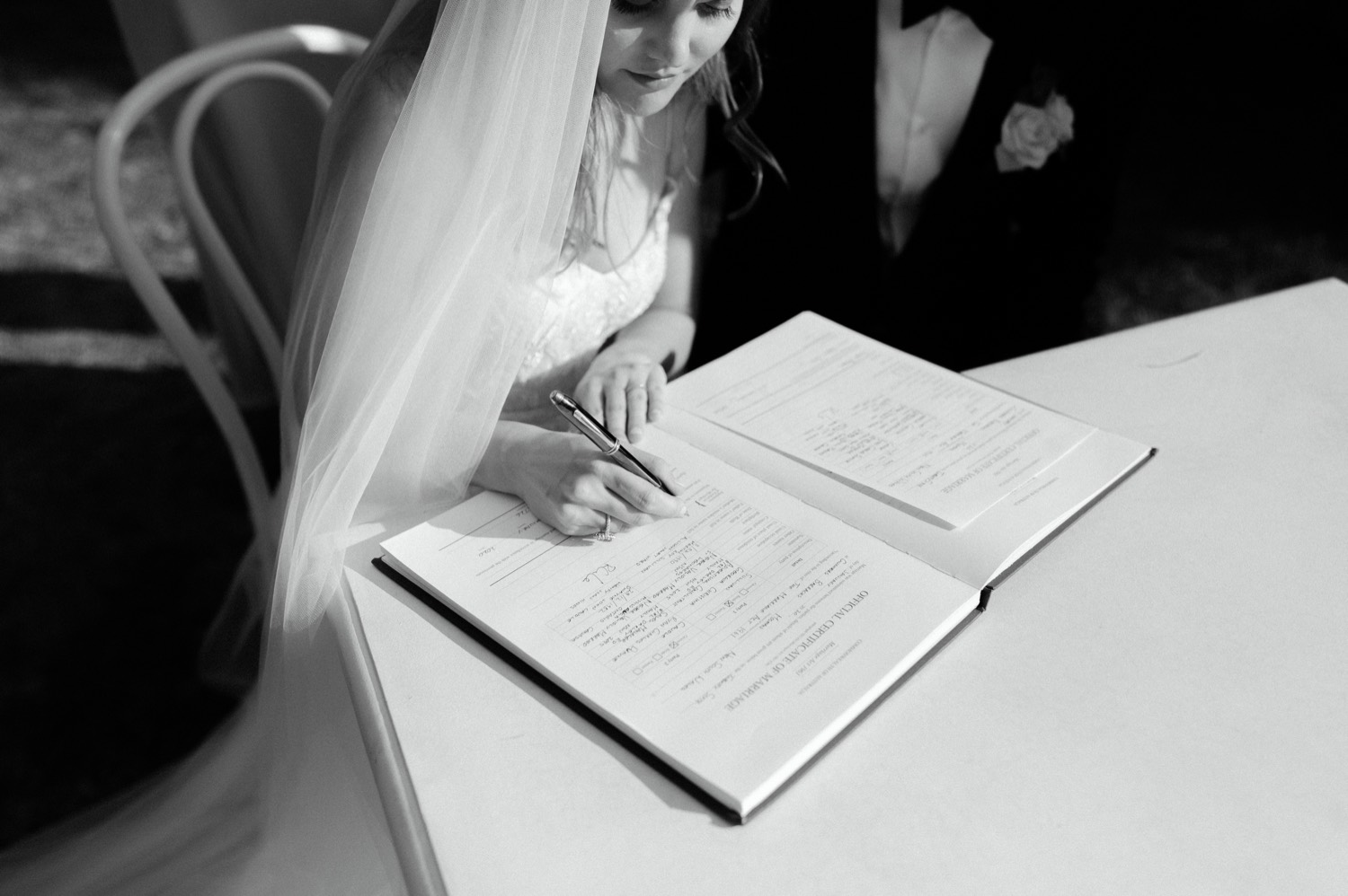 arty shot of bride signing wedding certificate