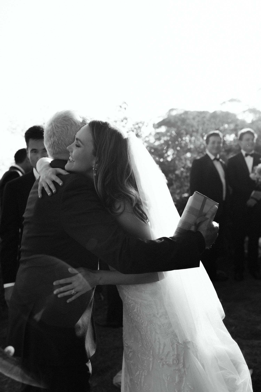 bridge hugging guests after wedding ceremony