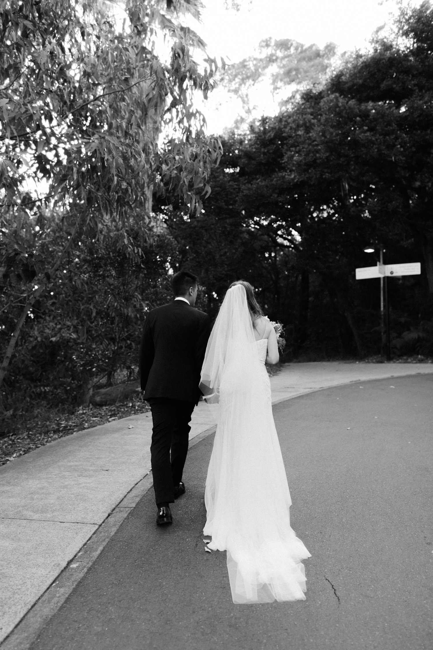 black & white shot of bride and groom walking up to georges head