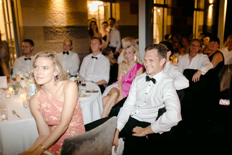 black tie wedding guests enjoying speeches